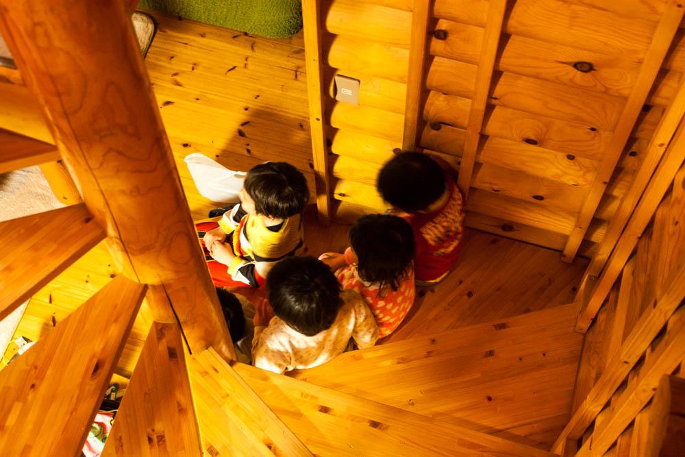コテージの螺旋階段に座る健康児